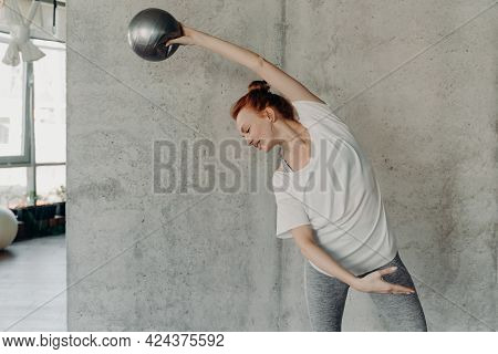 Active Slim Woman Doing Sport Exercises During Barre Workout, Arching Body On Side And Raising Hand