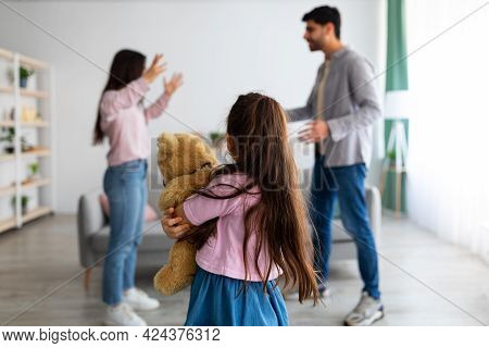 Family Quarrels Concept. Little Girl Suffering From Family Quarrels, Cuddling Her Teddy Bear And Tur