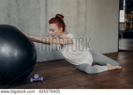 Active Female In White Tunic And Leggings With Fitness Pilates Ball And Dumbbells Performing Balance