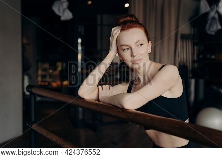 Young Attractive Slender Woman Ballerina With Red Hair Leaning On Ballet Barre In Meditative Facial