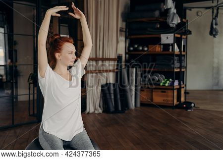 Sportive Gracile Young Woman With Red Hair Sits On Big Silver Pilates Ball With Hands Lifted Over He