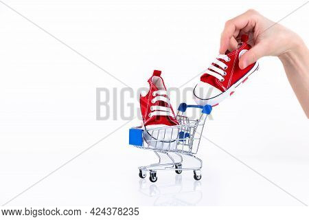 Female Hand Puts Baby Red Sneakers Into The Shopping Cart Isolated On White Background. Online Store
