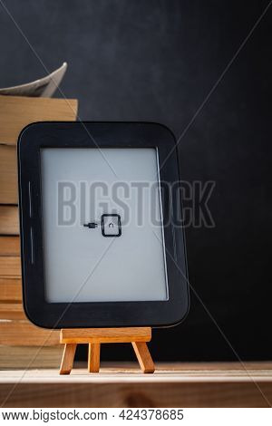 E-book Reader On The Wooden Stand Next To The Stack Of Paper Books At The Black Background.