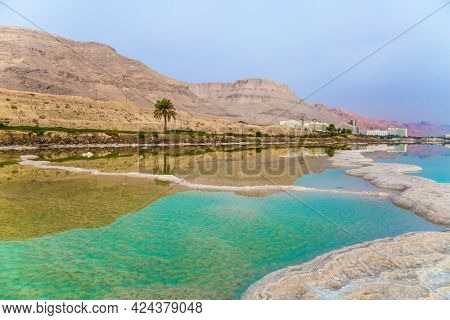 Israel. Early morning at the resorts of the Dead Sea. Picturesque white paths from evaporated salt. Azure sea water is full of healing salts. Concept of ecological, medical and photo tourism
