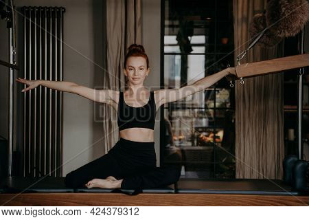 Healthy Redhead Female Sitting On Trapeze Table With Arms Outstretched To Both Sides In Relaxed Posi