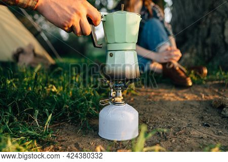 The Hand Of A Man Traveler Prepares Tea In A Geyser Coffee Maker On A Gas Burner In The Forest. Camp