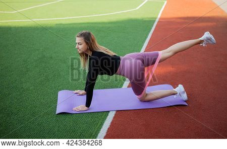 Young Fit Slim Woman In Sportswear Practices Exercise With Fit Elastic Bands On The Mat. Outdoor Tra