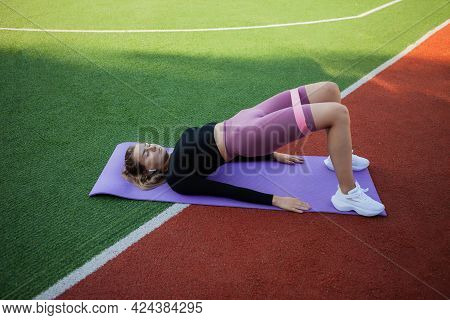 Young Fit Slim Woman In Sportswear Practices Exercise With Fit Elastic Bands Lying On The Mat. Outdo