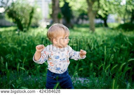 Kid Stands Among The Tall Grass With His Head Turned. Close-up
