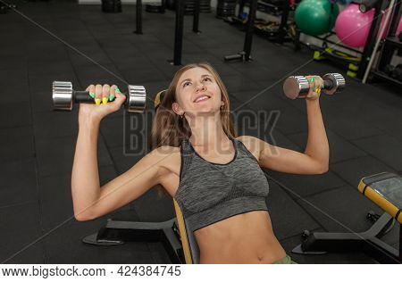 Attractive Young Fitness Woman Practicing Dumbbell Press Lying On An Incline Bench In The Gym