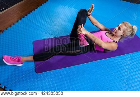 Active Blonde Woman On Mat Doing Warm-up Exercises. Fit Woman Lies On Yoga Mat And Practicing Stretc