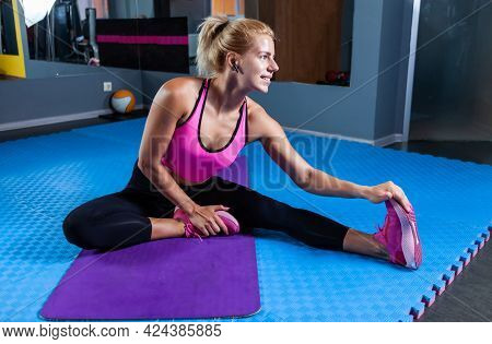 Healthy Blonde Fitness Woman On Mat Doing Warm-up Exercises. A Fit Woman Sitting On Yoga Mat And Pra