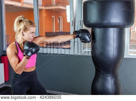 Woman Boxer In Boxing Gloves Punches A Punching Bag
