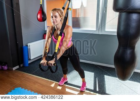 Sporty Women Training With Fitness Trx Straps In The Gym. Beautiful Lady Exercising Her Muscles Slin