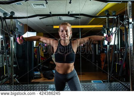 Slim Fit Blonde Woman Flexing Muscles On Gym Machine. Girl Execute Exercise With Exercise-machine Ca