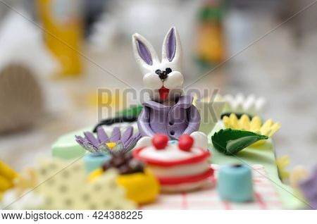 Edible Purple Bunny Figurine Made Of Sugar Paste Or Fondant Icing On A Cake Close-up