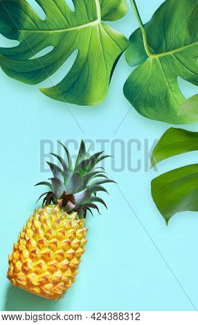 Yellow Pineapple And Palm Leaf On A Blue Background. Exotic Concept.