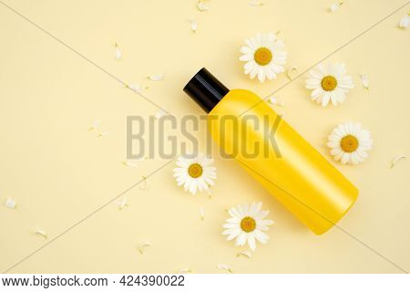 Bottle Of Mockup Cosmetic Products With Chamomile Flowers On A Yellow Background. Cosmetics With Cha