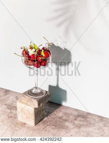 Summer Composition With A Glass Filled With Cherries On The Cement Podium, And Shade Of Palm Tree On