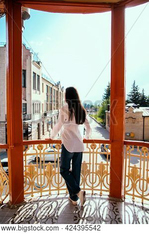 A Young Woman Looks Out From The Balcony.the Bright Sun Illuminates The Girl Who Is Standing With He