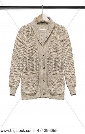 Beige Knit Cardigan Hanging On Wooden Clothes Rack Isolated Over White