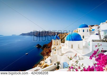 View Of Traditional Greek Village Oia Of Santorini, With Blue Domes Against Sea And Caldera, Greece