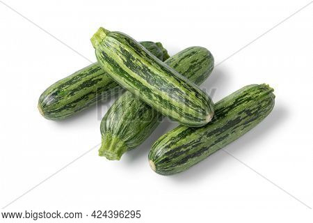 Heap of fresh raw green spotted courgette close up isolated on white background