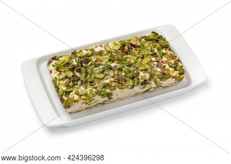 Plate with traditional Turkish pistachio halva on a plate close up isolated on white background