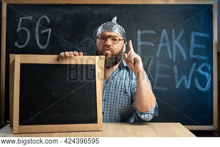 A Conspiracy Theorist In A Protective Aluminum Foil Hat And Glasses Sits At A Table And Points His F
