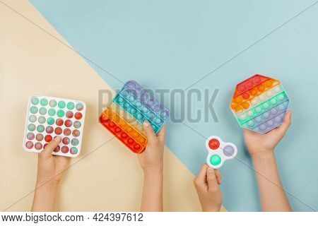 Many Hands Holding Trendy Pop It Fidget Toys On Colorful Background. Push Pop-it Fidgeting Game Help