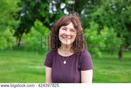 Happy Woman On The Park. Portrait Of Beautiful Female, The Wind Fluttering Hair. Summer Portrait On