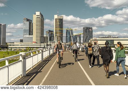 Vilnius, Lithuania - May 30, 2021: People Walking, Riding Bikes And Scooters On White Bridge. Vilniu