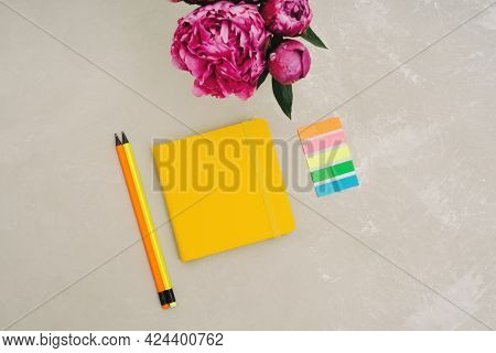 Back To School. Stationery For Schoolchildren And Students. A Bouquet Of Pink Peonies, A Yellow Note