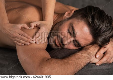 A Good-looking Man Getting A Back Massage Lying Down At Spa, Woman Hand Making Sign Heart Love Conce