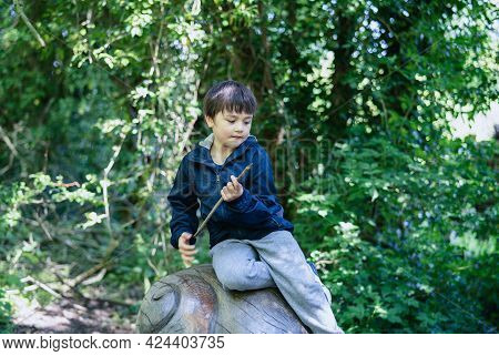 Portrait Active Kid Sitting On A Wooden Statue At Public Park,happy Child Wearing Blue Jacket Playin