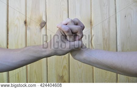The Hand Of A Man And A Woman Locked In A Close-up On A Wooden Background.