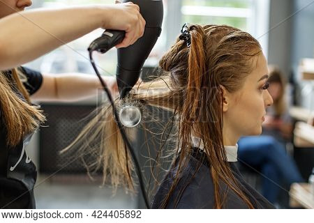Barber Dries His Hair. A Girl In A Beauty Salon, A Hairdresser Does Her Hair, Cuts Her Hair To A Gir