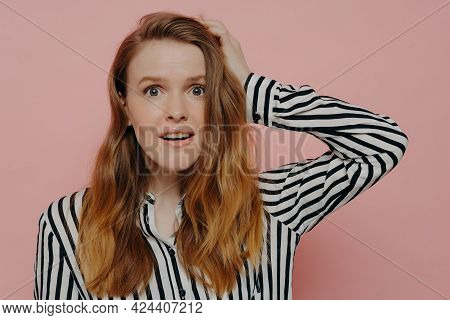 Attractive Young Female In Stripy Black And White Blouse Touching Head With One Hand In Astonishment