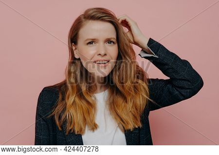 Attractive Pensive Young Woman With Wavy Ginger Hair In Formal Dark Jacket And White Top Thinking Wh