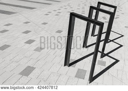 Bicycle Parking Structures Made Of Steel Stand In A Cobbled Stone Road Pavement, Abstract Urban Tran
