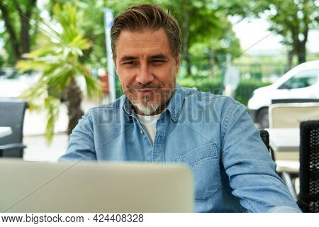 Outdoor portrait of mid adult man in 50s, happy confident smile. Working with laptop computer. Mature age, middle age, bearded.
