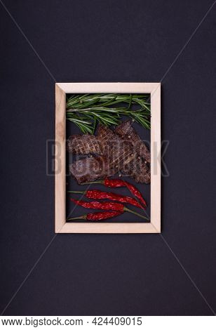 Jerky Snacks, Red Papper And Rosemary Inside Of Wooden Frame On Black Background. Creative Concept W