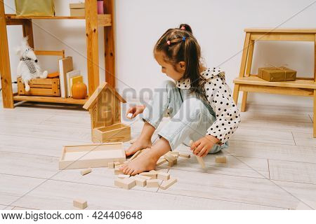 A Girl With Two Ponytails On Her Head Sits On The Floor In Her Room And Plays With Wooden Cubes. The
