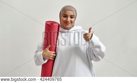 Smiling Young Arabic Woman Holding Sport Mat And Showing Thumb Up While Posing On Light Background W