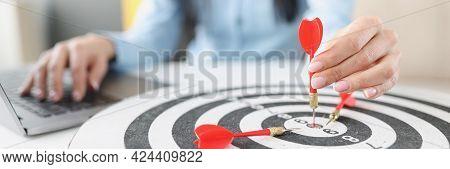Female Hand Holding Dart In Dart Center At Work Table