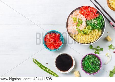 Poke, One Of The Main Dishes Of Hawaiian Cuisine. Bowl With Bulgur, Shrimp, Chuka Salad. On A Gray W