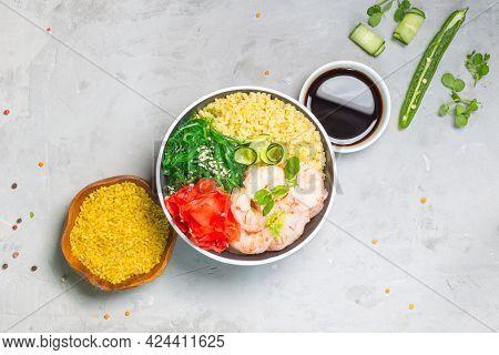 Poke, One Of The Main Dishes Of Hawaiian Cuisine. Bowl With Bulgur, Shrimp, Chuka Salad. On A Gray B