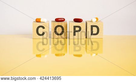 Word Copd Is Made Of Wooden Cubes On A Yellow Background With Pills. Medical Concept Of Treatment, P