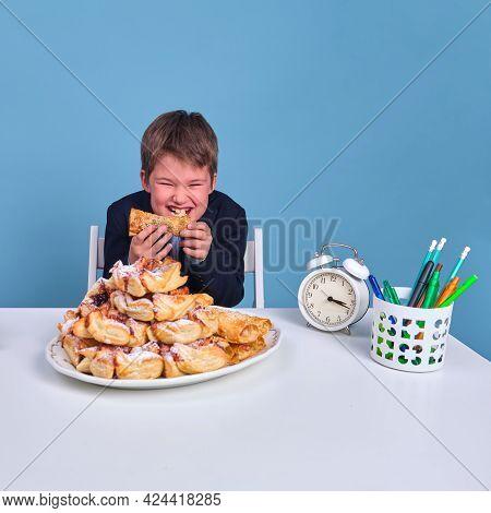 Happy Pupil Boy Junior Eating Unhealthy Sweet Food At School Desk