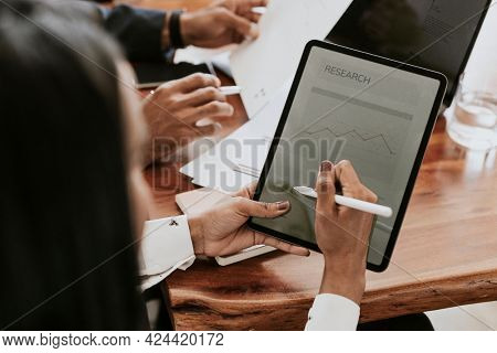 Businessperson taking note on a digital tablet